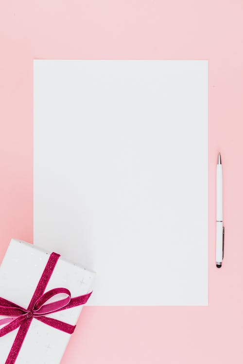 Close-Up Shot of a White Bond Paper and a Pen beside a Gift Box on a Pink Surface