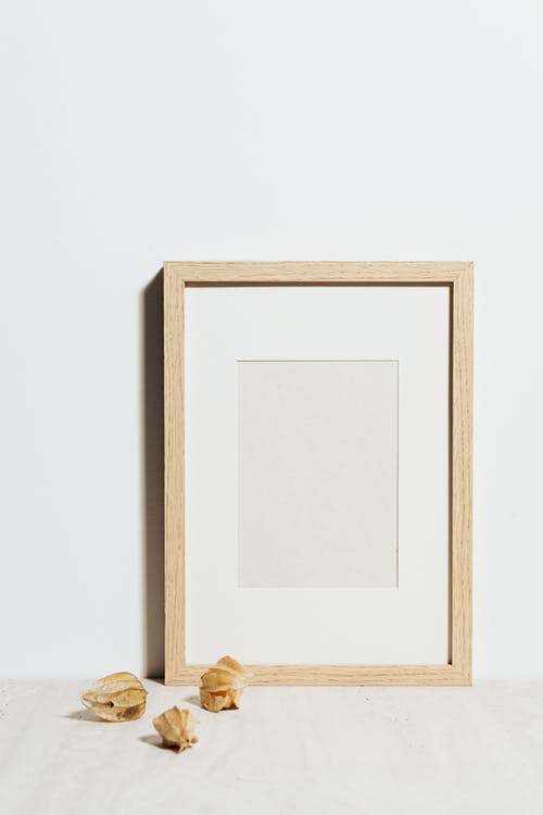 Close-Up Shot of a Wooden Frame beside a White Wall