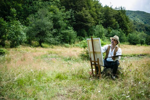 Man in White Dress Shirt Doing Canvas Painting On A Grass Field
