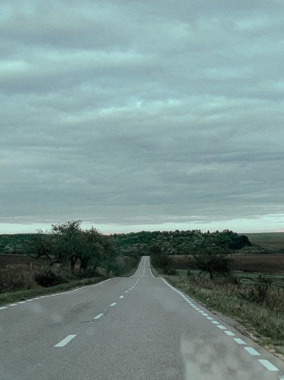 Empty paved road running through fields