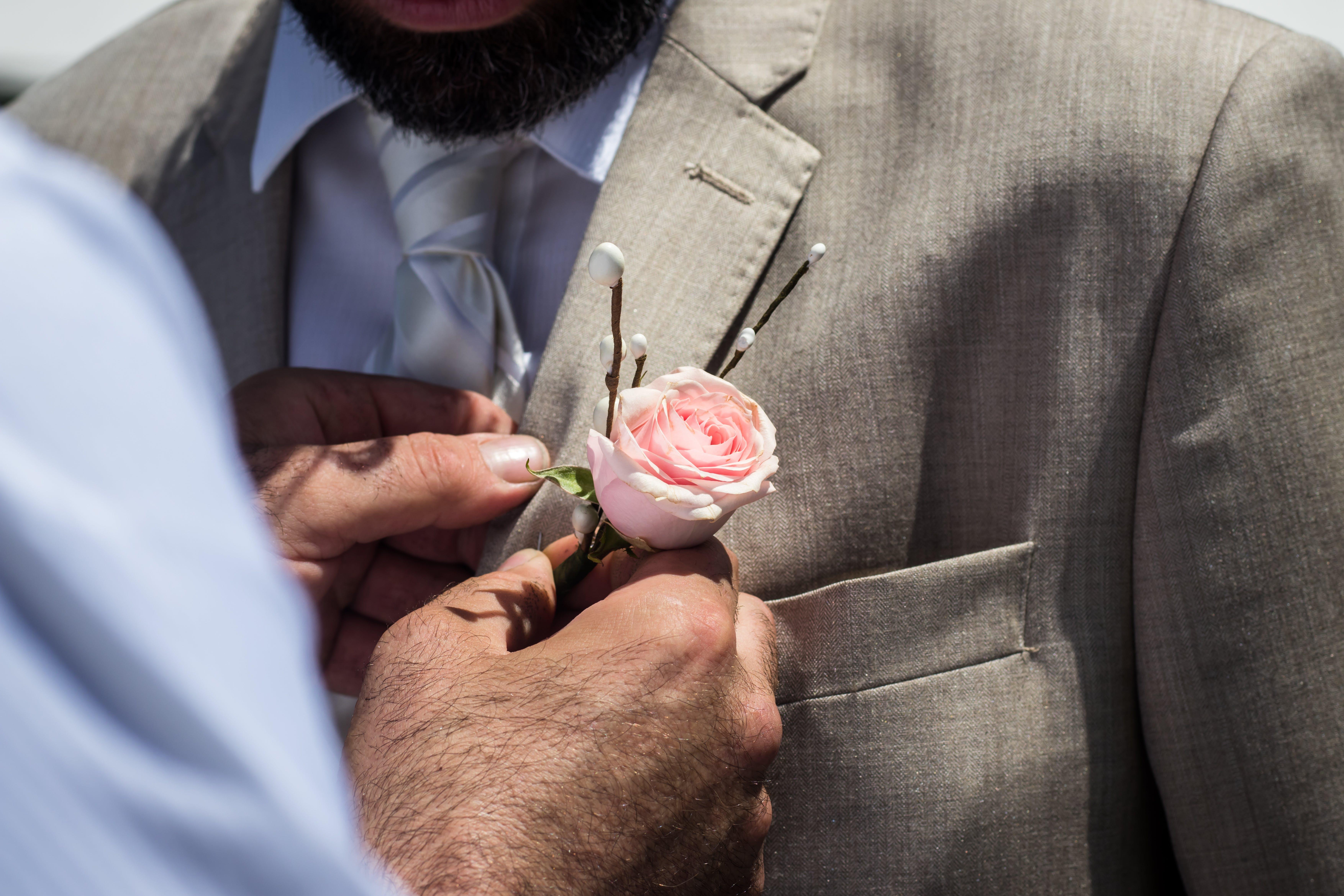 Man Pinning Pink Rose on Man's Collar