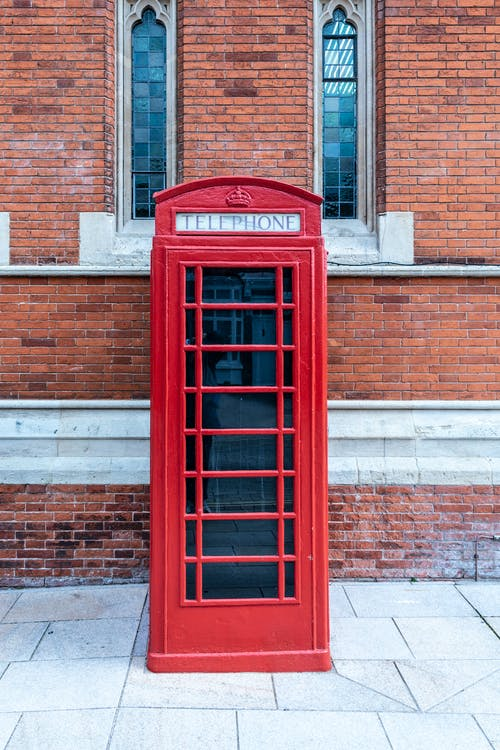Red Telephone Booth Beside Brown Brick Building