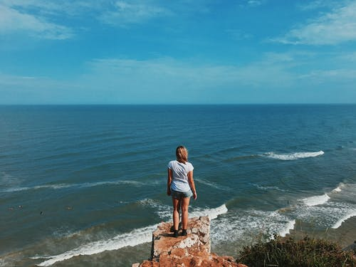 Anonymous woman standing on rocky cliff against endless blue sea