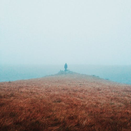 Anonymous person standing on mystic foggy seashore