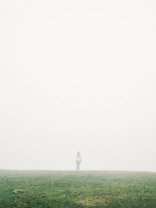 Faceless lonely woman standing on meadow in thick fog