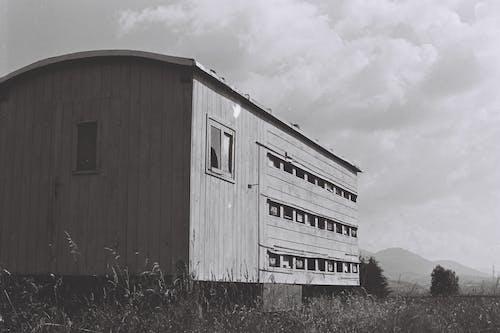 An Abandoned Wooden Farmhouse On Grass Field