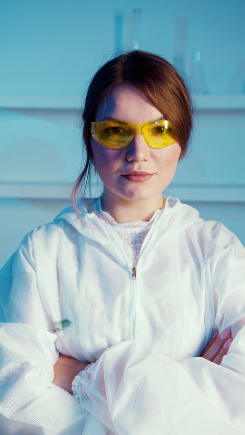 A Woman Wearing a White Lab Coat and Orange Protective Goggles