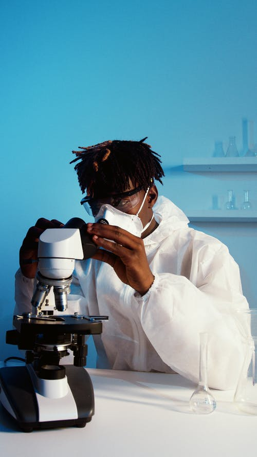 A Man Looking Through the Microscope