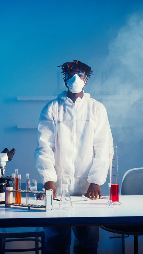 A Man Wearing Face Mask and Lab Coat While Standing by the Table With His Experiments