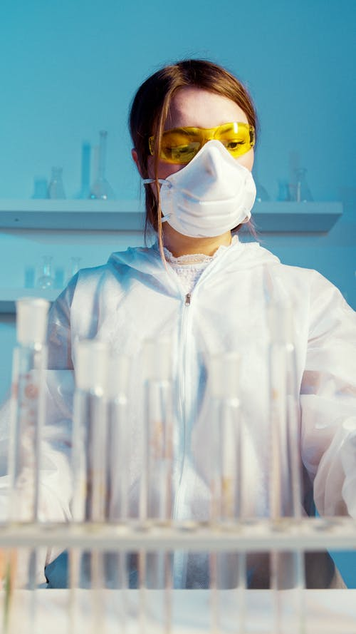 A Woman Wearing a Face Mask and Lab Coat While Doing an Experiment