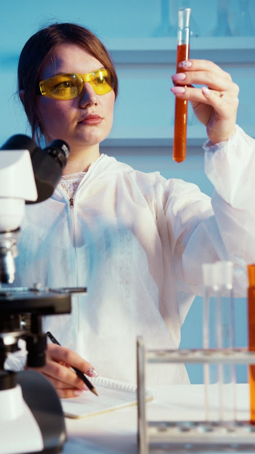 A Woman Holding While Looking at a Test Tube