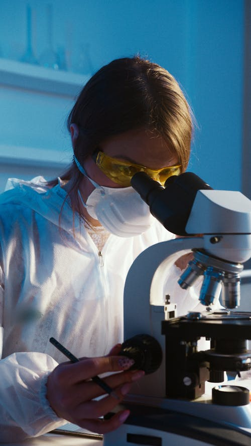 A Woman Looking Through the Microscope