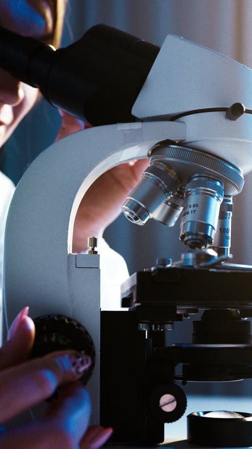 Close-Up View of a Person Looking through the Microscope
