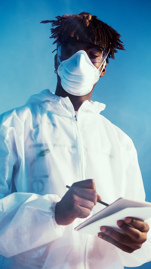 A Man Wearing a Face Mask and Notebook While Looking at the Camera