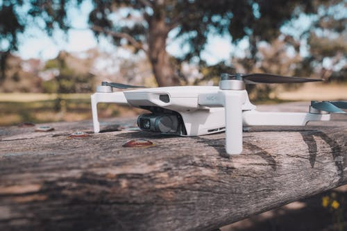 White and Black Drone on Wooden Table