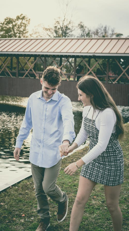 Happy young boyfriend and girlfriend strolling on lawn with fresh green grass near water of pond