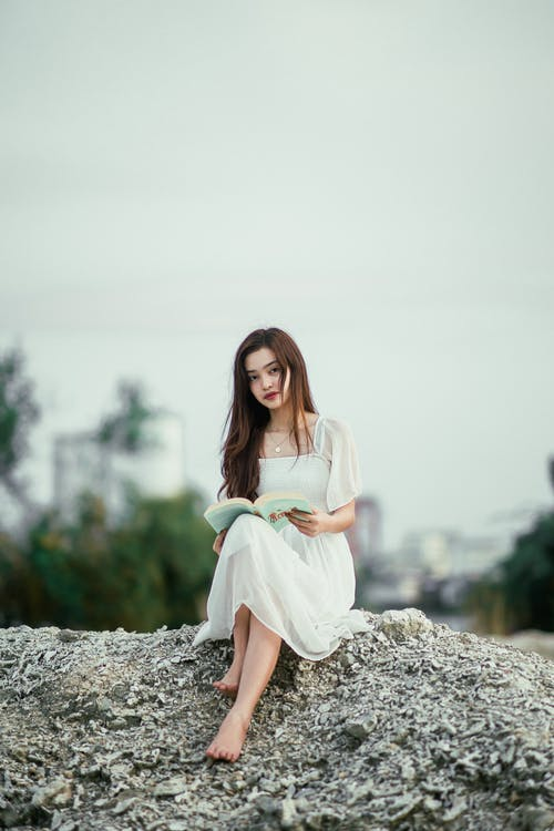 Young elegant Asian female in dress with textbook sitting on rough terrain and looking at camera in town