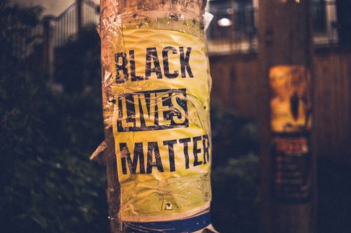 Inscription of protest movement saying black lives matter on pole in city street in evening