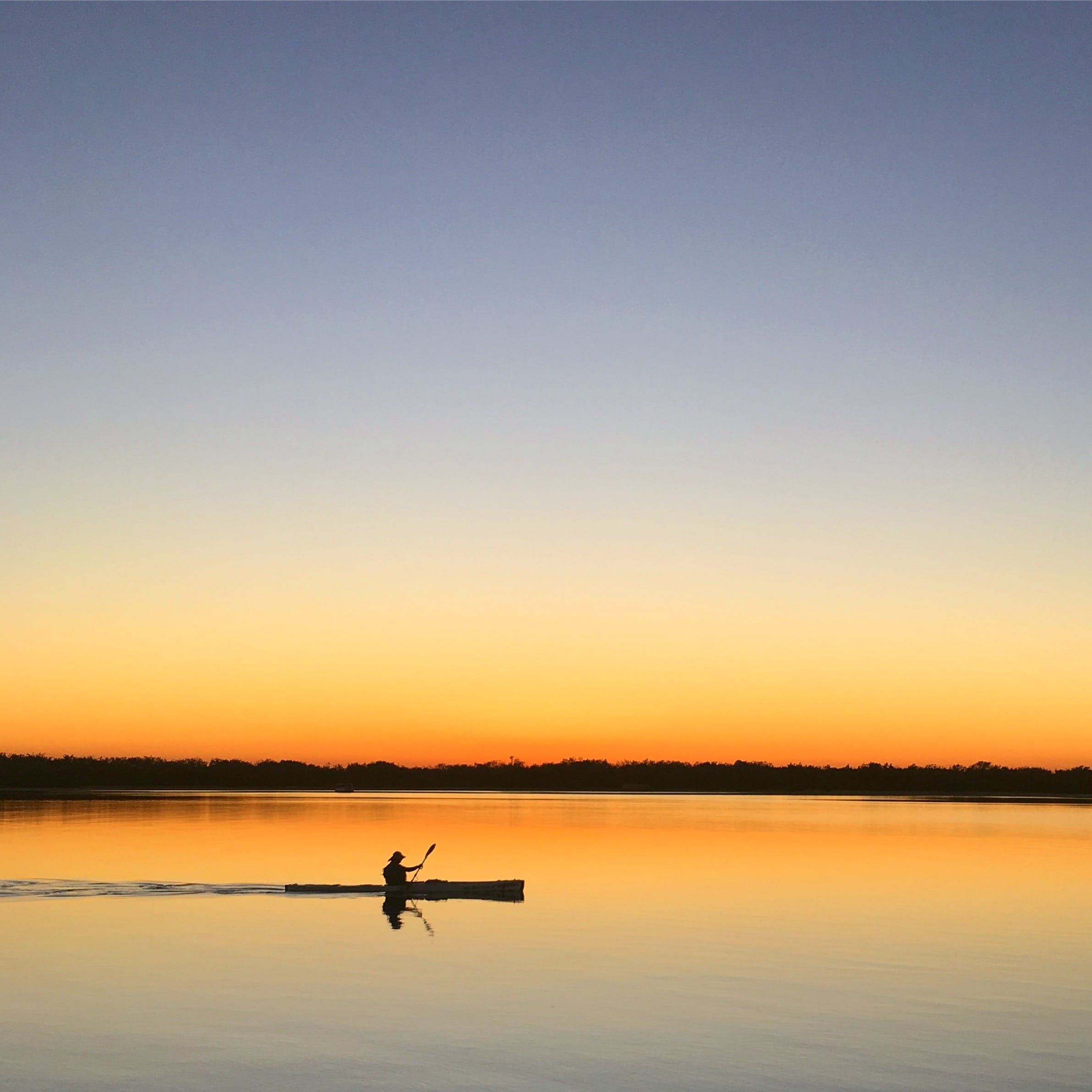 Silhouette of Man Inside of Boat Sailing on Body of Water during Sunset