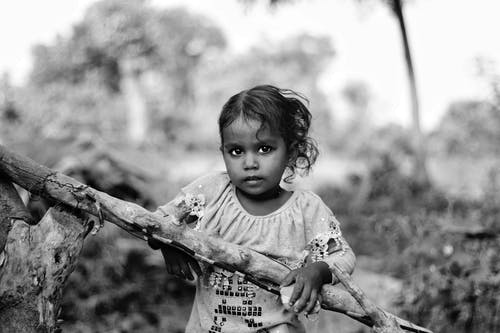 Grayscale Photo of Girl Holding a Stick