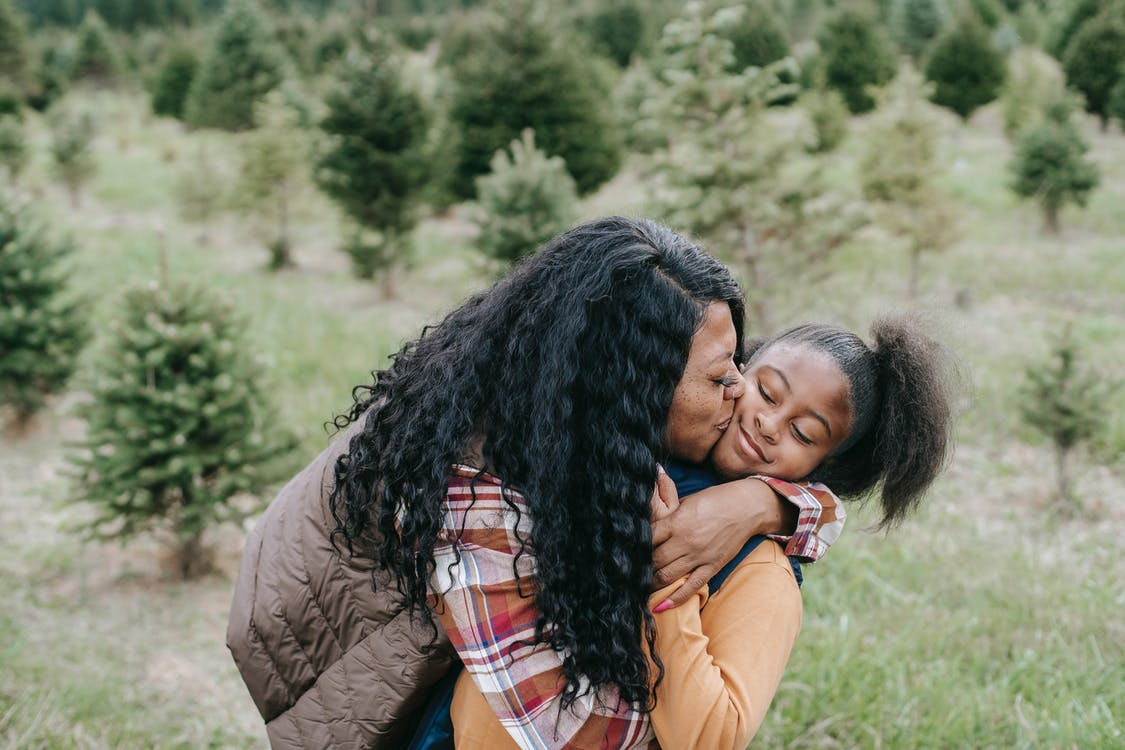 Loving African American mom hugging daughter and kissing while standing among green fir trees