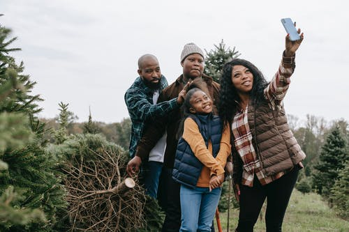 Happy black family taking selfie on smartphone