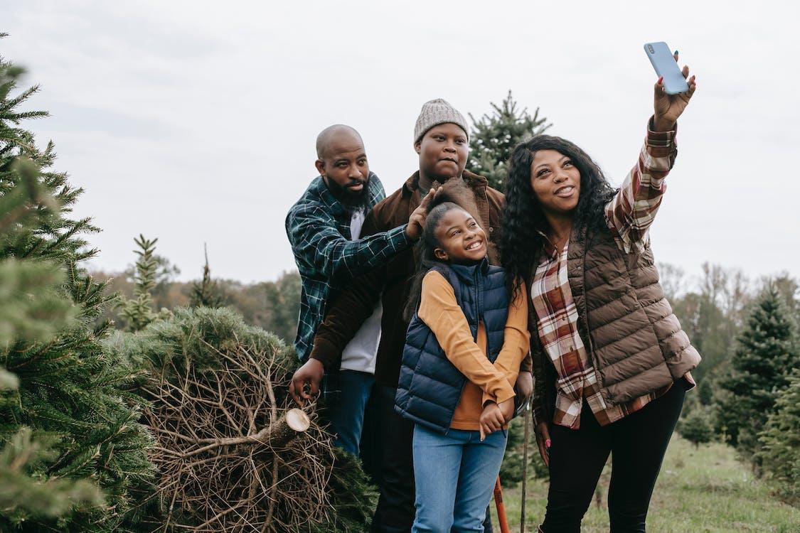 Happy black family taking selfie on smartphone