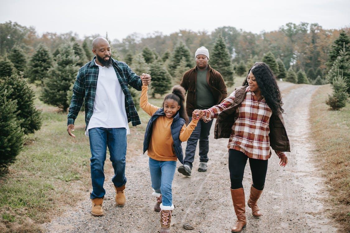 Smiling ethnic family walking on tree farm road