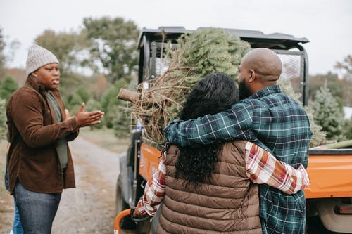 Unrecognizable black parents interacting with son near ATV on farm