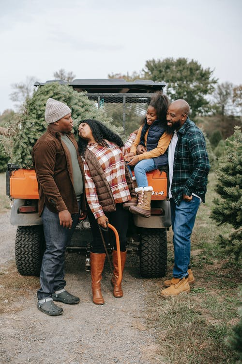 Black family near quad bike on tree farm
