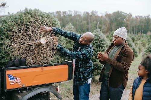 Black man putting Christmas tree in back of ATV