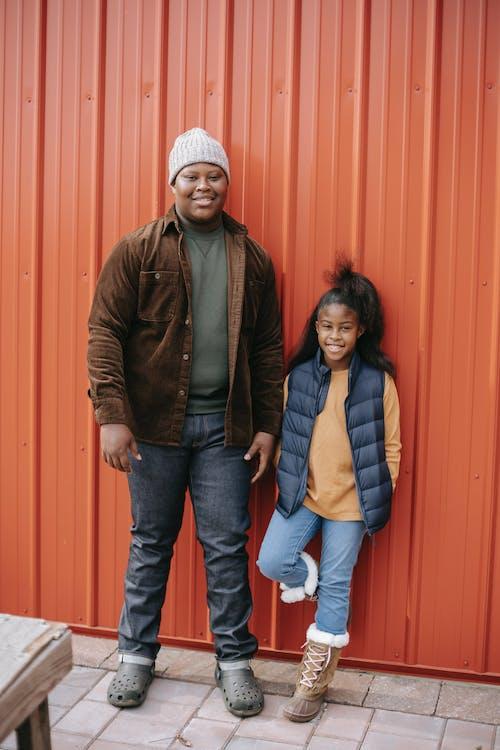 Smiling black siblings near metal fence in daylight