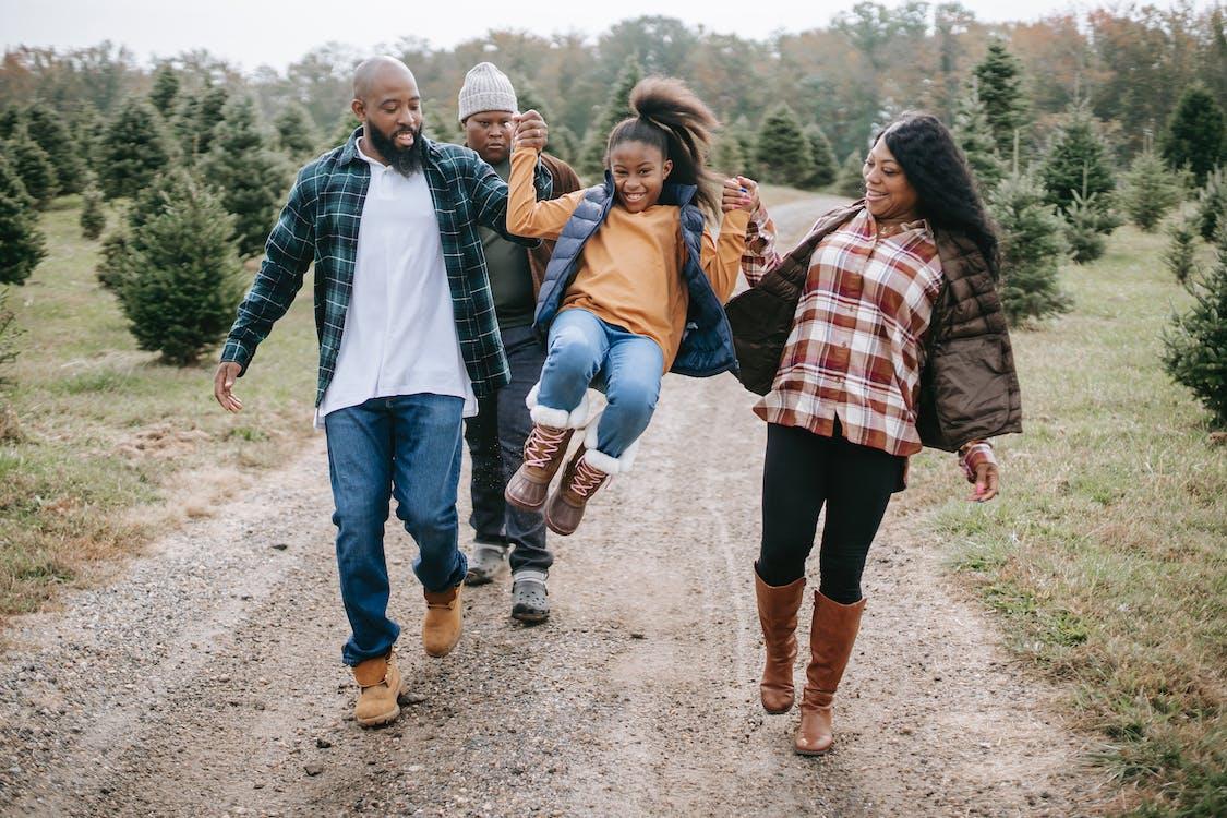 Ethnic parents raising cheerful girl on tree farm roadway
