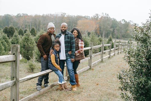 Young content African American parents embracing daughter and son near wooden fence on tree farm while looking at camera