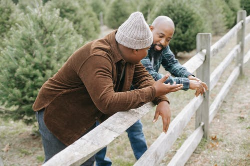 Black father talking to unrecognizable son near fence in countryside