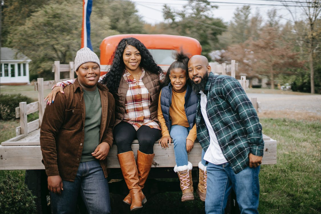 Cheerful African American family embracing near vehicle on farm