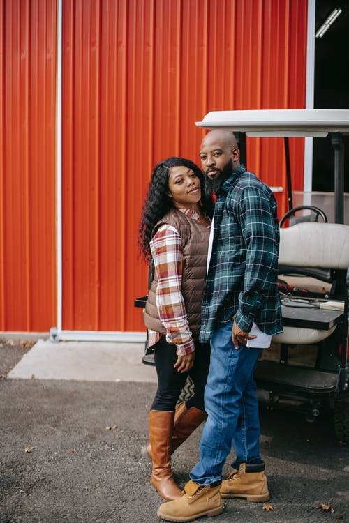 Black couple standing close near vehicle and fence