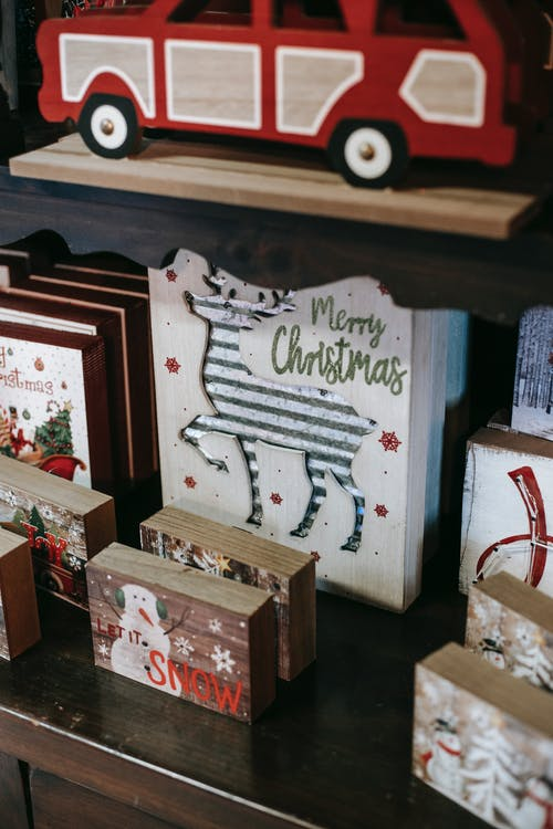 Collection of decorative Christmas boxes on wooden shelves