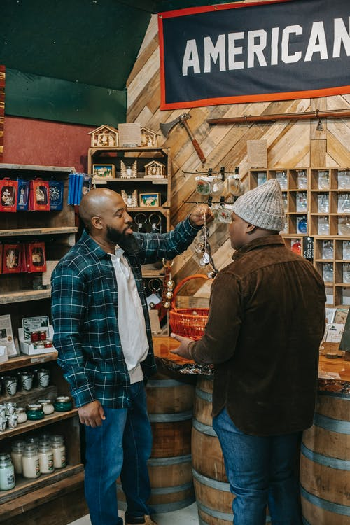 Black father with unrecognizable son choosing souvenirs in local shop