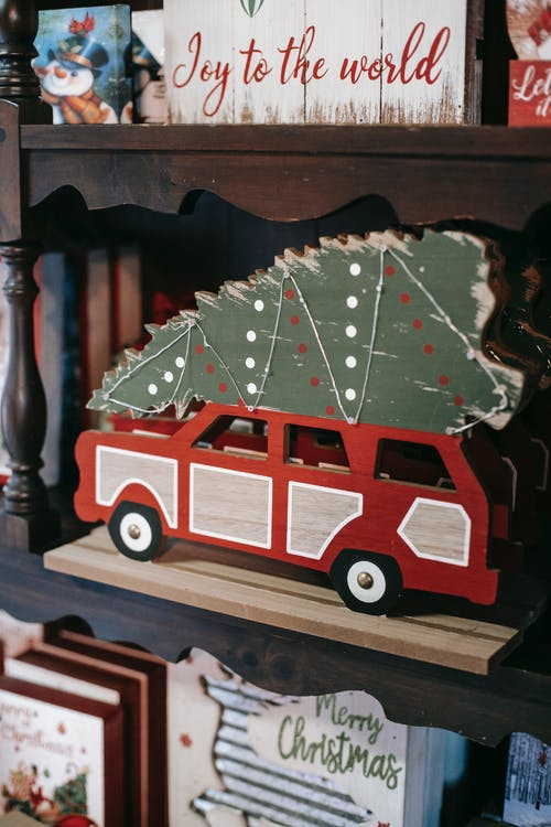 Bright wooden transport with Christmas tree near decorative boxes with festive inscriptions during New Year holiday