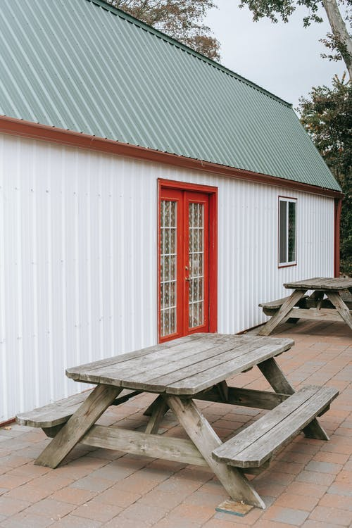 House facade near wooden tables with benches