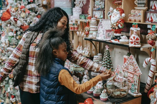 Happy black mother with daughter choosing souvenirs in shop