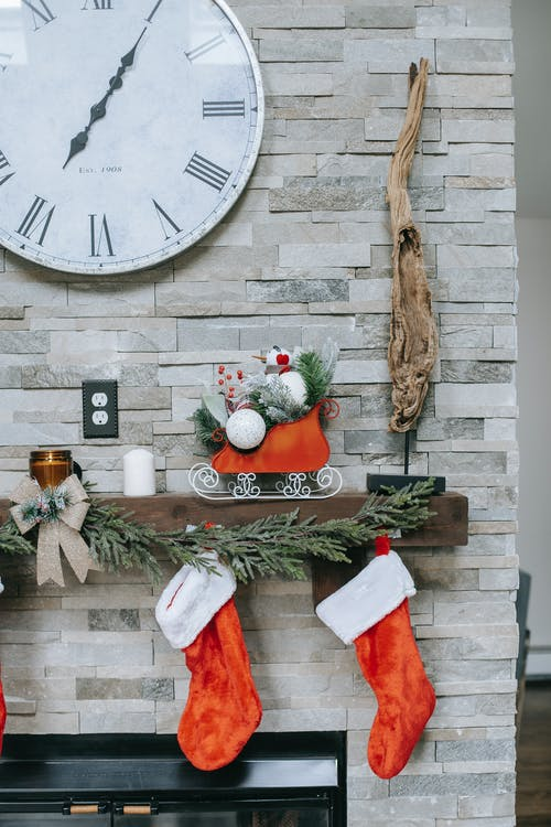 Round clock on wall over shelf with decorative Christmas socks and bright sleigh in house