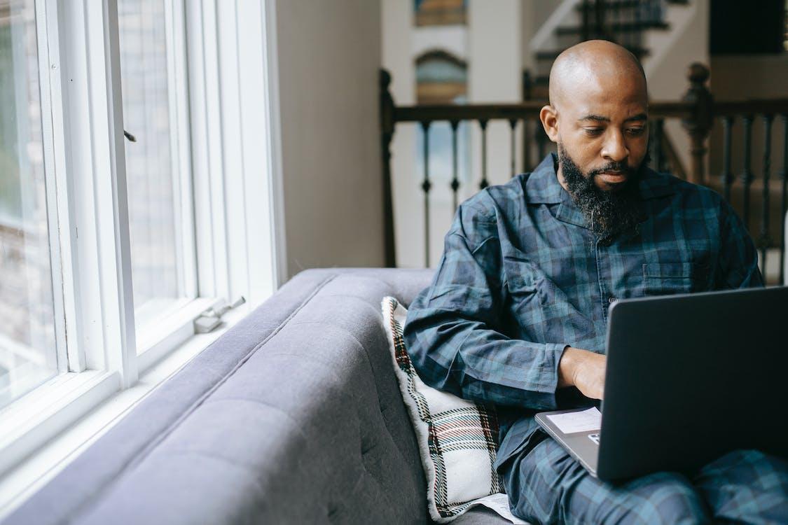 Serious black man using laptop at home
