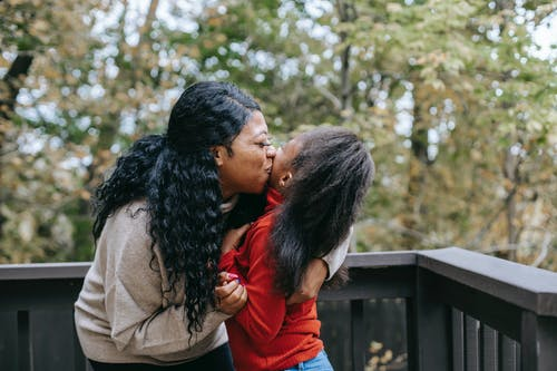 Side view of loving cheerful African American mum hugging and kissing girl standing on terrace