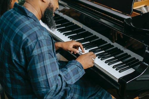 Bearded black male musician playing piano