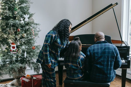 Back view of anonymous African American family playing musical instrument in cozy room with decorated Christmas tree