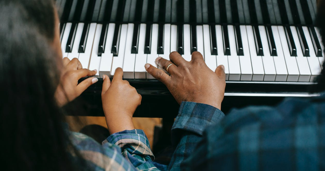 From above of crop anonymous African American man playing musical instrument with girl while rehearsing together