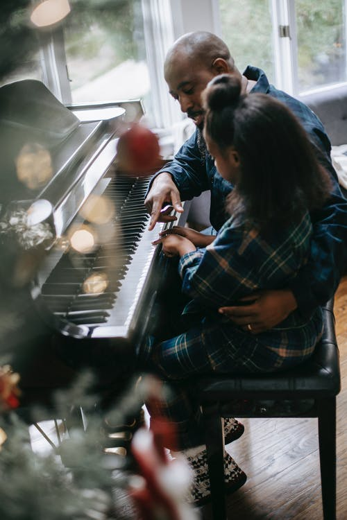 Side view high angle of African American father and daughter playing acoustic piano during Christmas celebration