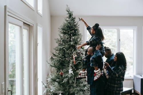 Девушка кладет рождественскую звезду на елку
